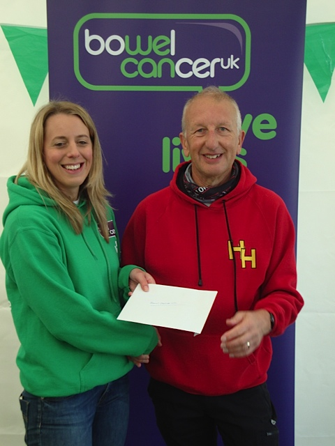 Harriers Chairman Tony Essex presenting a cheque to Bowel Cancer UK